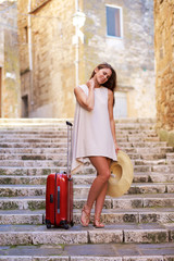 Young woman suffers from back pain lifting a heavy suitcase