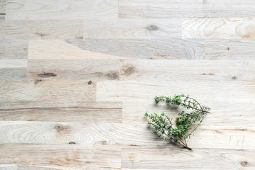 fresh branch of thyme on an oak tree cutting board seen from the top