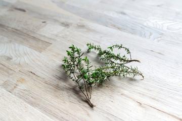 fresh branch of thyme on an oak tree cutting board
