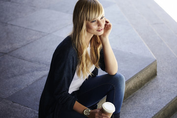 Wall Mural - Beautiful blond woman sitting on steps