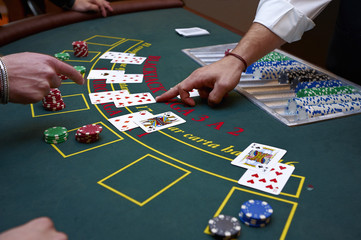 A close up of a blackjack dealer's hands in a casino, very shallow depth of field