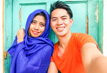 Young asian muslim couple taking selfie next to old green wooden door - Cheerful teenagers of different religion posing for self photo - Portrait of mixed culture students -