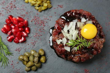 Delicious beef tartare with ingredients, closeup