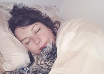 süßes Kätzchen schläft im Bett mit Besitzer