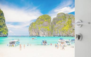 opened white door to beautiful beach with tourist at maya bay, phi phi leh island, thailand