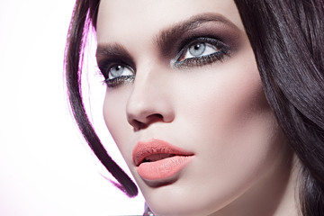 beautiful girl with smoky eyes on the pink background looking up