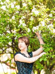 Beautiful young asian woman in flowering spring garden.
