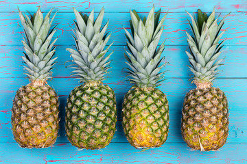 Four pineapples beside each other on table