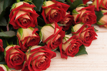 Beautiful red roses on a dark wooden table