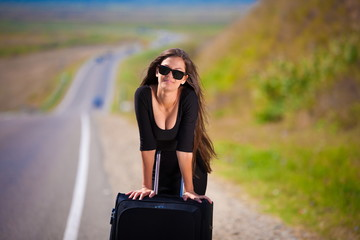 brunette woman road suitcase