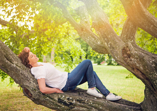 woman relaxing on a big branch of a tree