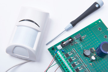 Connecting motion infrared detector to an alarm main board. Safety and surveillance concept.