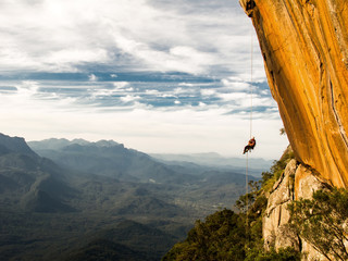 Abseiling a negative yellow rock wall with mountains on backgrou