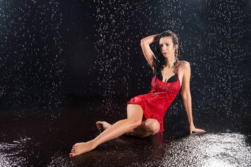 Sexual woman in red dress under water drops
