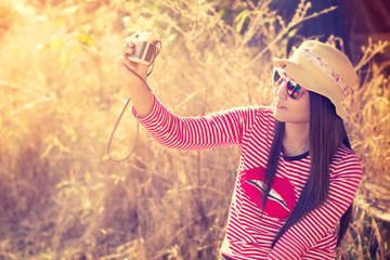Hipster teen girl with camera and selfie - vintage color effect retro style