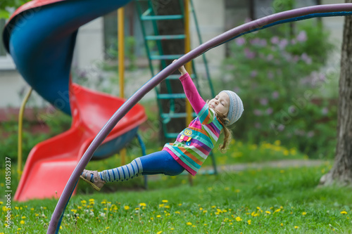 Active little girl hanging on jungle gym outdoors on spring playground