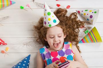 Little girl on wooden floor making selfie in birthday party.