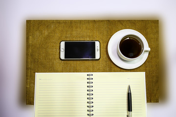 coffee in white cup with smart phone and notebook on brown and white background