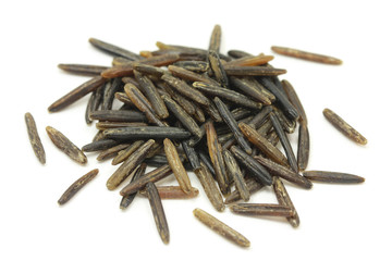 pinch grains of wild rice on a white background