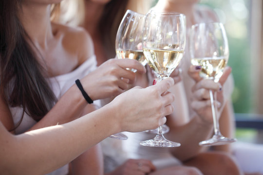 Happy friends toasting wine