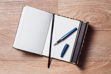 Open notebook and pen on the wooden background