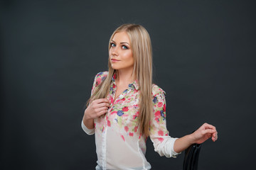 Attractive young blonde woman in transparent colorful blouse posing on gray background