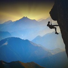 Climber on a cliff against misty mountains
