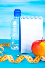 Workout and fitness diet. Healthy lifestyle concept. Apple, bottle of water, measuring tape, notebook.