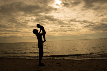 Father and son playing on the beach at the sunset time. Concept