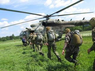 парашютисты садятся в вертолет для десантирования