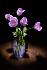 Bouquet of pink tulips in glass vase on black background