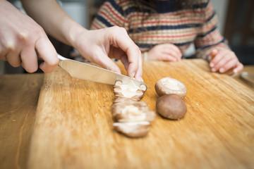 椎茸を切る母とそれを見る子供