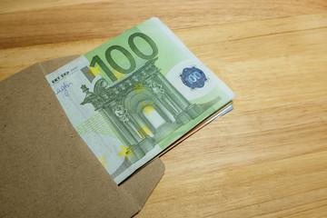 Euro banknotes in salary brown envelope.