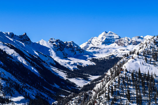 The Rocky Mountains of Colorado, with the Maroon Bells Peak, as viewed from the top of the Aspen/Snowmass ski resort on a clear winter day.