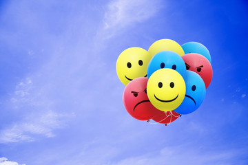 Bright balloons flying in the blue sky with a smiley