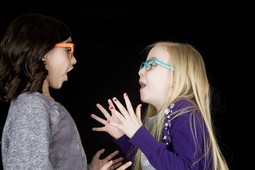 Two adorable girls wearing funky glasses drama in expression