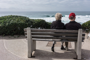 Older Couple Sitting on Bench Looking at Ocean