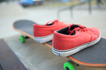 sneakers and skateboard at skatepark