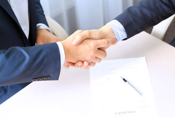 Close-up image of a firm handshake between two colleagues after