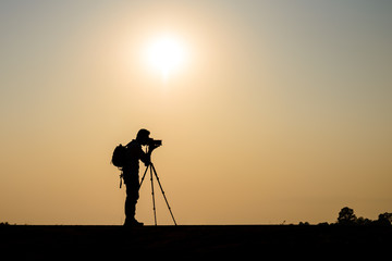 Silhouette photographer in sunset background