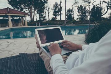 プールサイドでパソコンを操作する男性