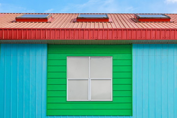 Painted colorful wall of residential building against blue sky.