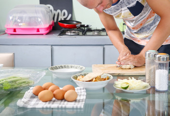 Man preparing meal in the kitchen - cutting tempeh