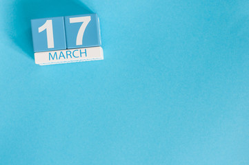 Happy St Patricks Day save the date. March 17th. Image of march 17 wooden color calendar on blue background.  Spring day, empty space for text