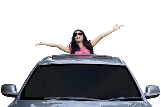 Woman standing on the sunroof of car
