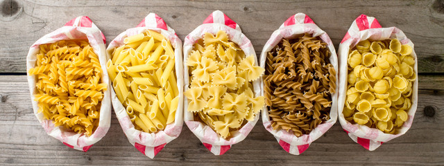 Pasta in paper bag on wooden table