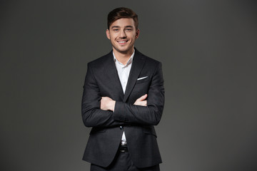 Cheerful successful young businessman standing with arms crossed