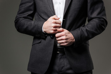 Hands of handsome businessman in black suit and white shirt