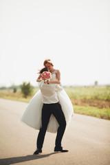 Beautiful wedding couple, bride and groom posing on road