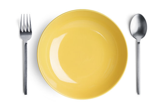 A yellow plate with silver fork and spoon